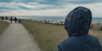 Lonely hooded female person from behind standing at seashore